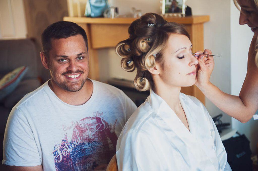 Brides brother happy behind makeup application