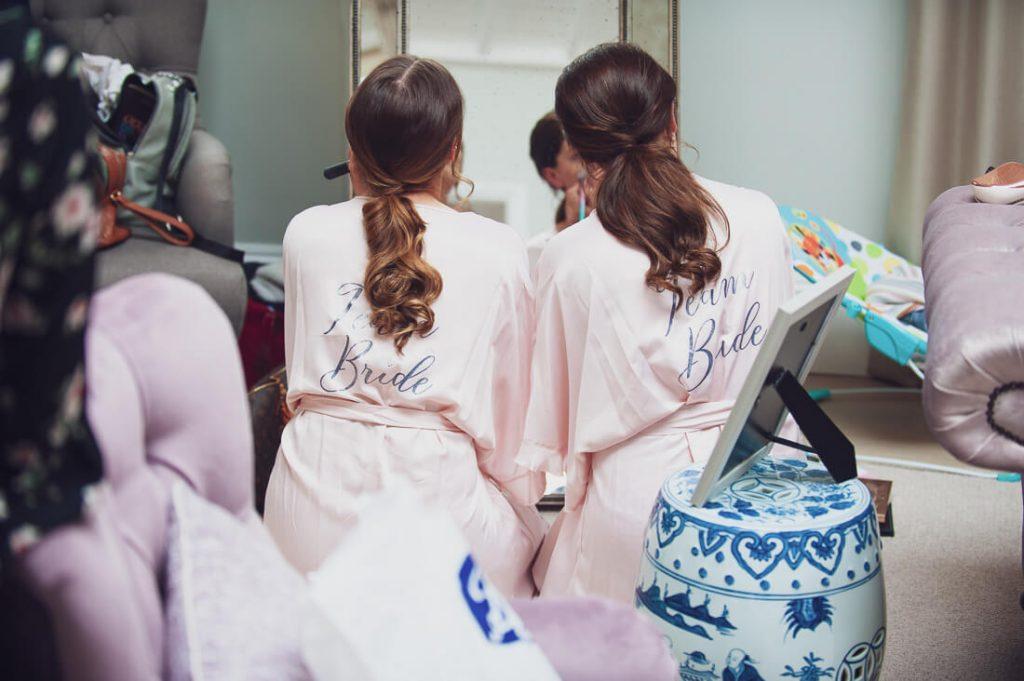 Bridesmaids applying makeup in mirror