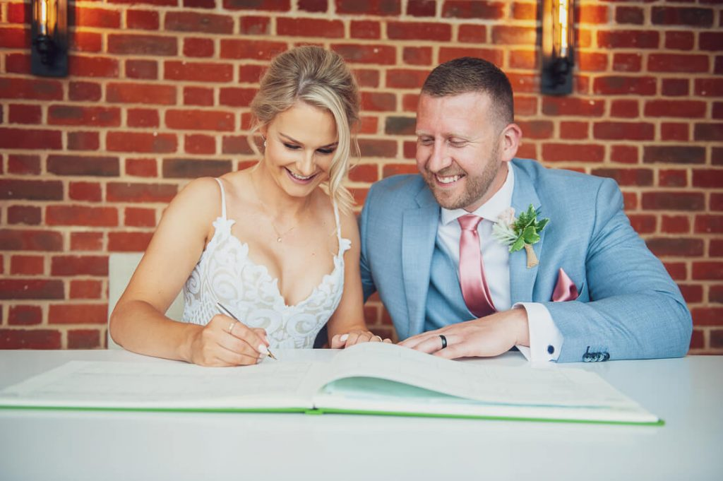 Happy couple sign the register